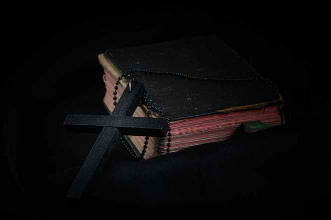 black cross leaning on black hardcover bible